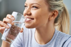 woman drinking water smiling