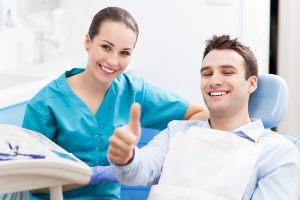 man in dentist chair giving thumbs up