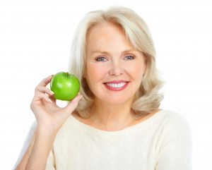 older woman smiling holding an apple