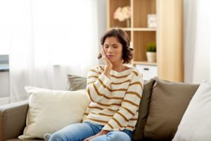 Woman wearing a striped sweater is sitting on a brown couch holding her cheek in pain