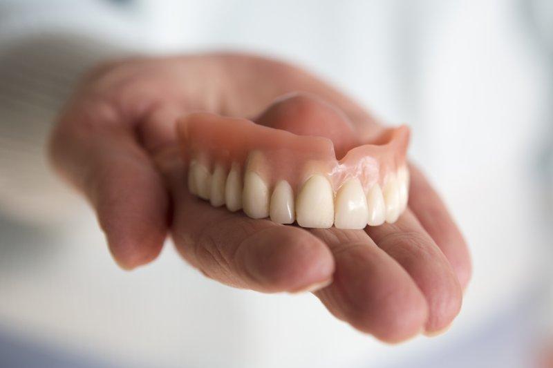 Person holding dentures in Allentown