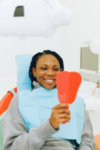 Smiling woman in dental chair holding mirror